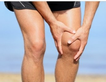 man holding his knee with both hands, symbolizing the causes of chronic knee pain