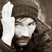 homeless man on a city street holding his hand on his head symbolizing a fear of failure and the consequenzes