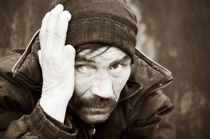 homeless man on a city street holding his hand on his head symbolizing a fear of failure and the consequences