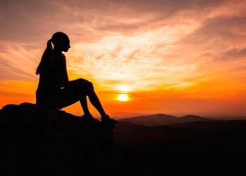 a woman sitting on a hill in the sunset, A simple, yet effective, technique to begin communicating with your spirit guides