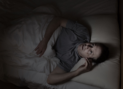 man suffering under chronic insomnia, the past life connection