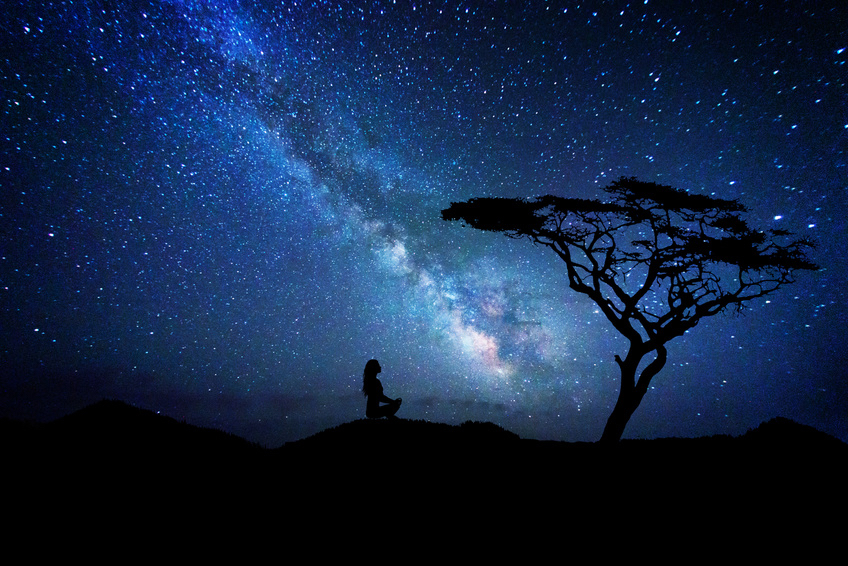 Woman silhouette near a tree meditates under the milky way galaxy, Your Soul's Cosmic Journey