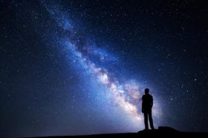man looking up to night sky, pondering past lifetimes