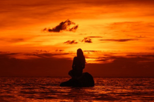 woman sitting on a rock in the middle of the ocean, studying the meaning of life