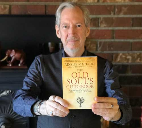 past life psychic Ainslie MacLeod with his book The Old Soul's Guidebook